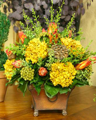 This elegant fall centerpiece will add charm to any room with its warm mixture of preserved gold hydrangea, preserved red protea, brunia and lepto.